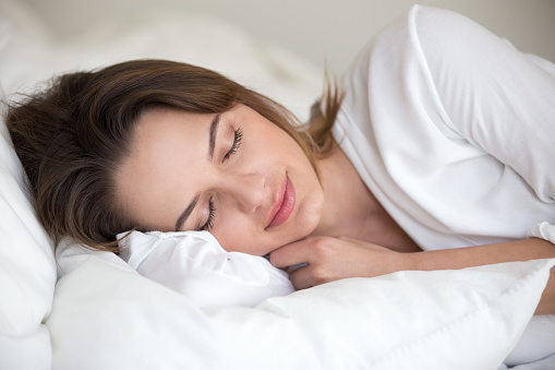 Young woman with beautiful face sleeping well on white cotton sheets and soft pillow lying asleep in comfortable cozy bed at home or hotel enjoying healthy nap resting enough for good relaxation
